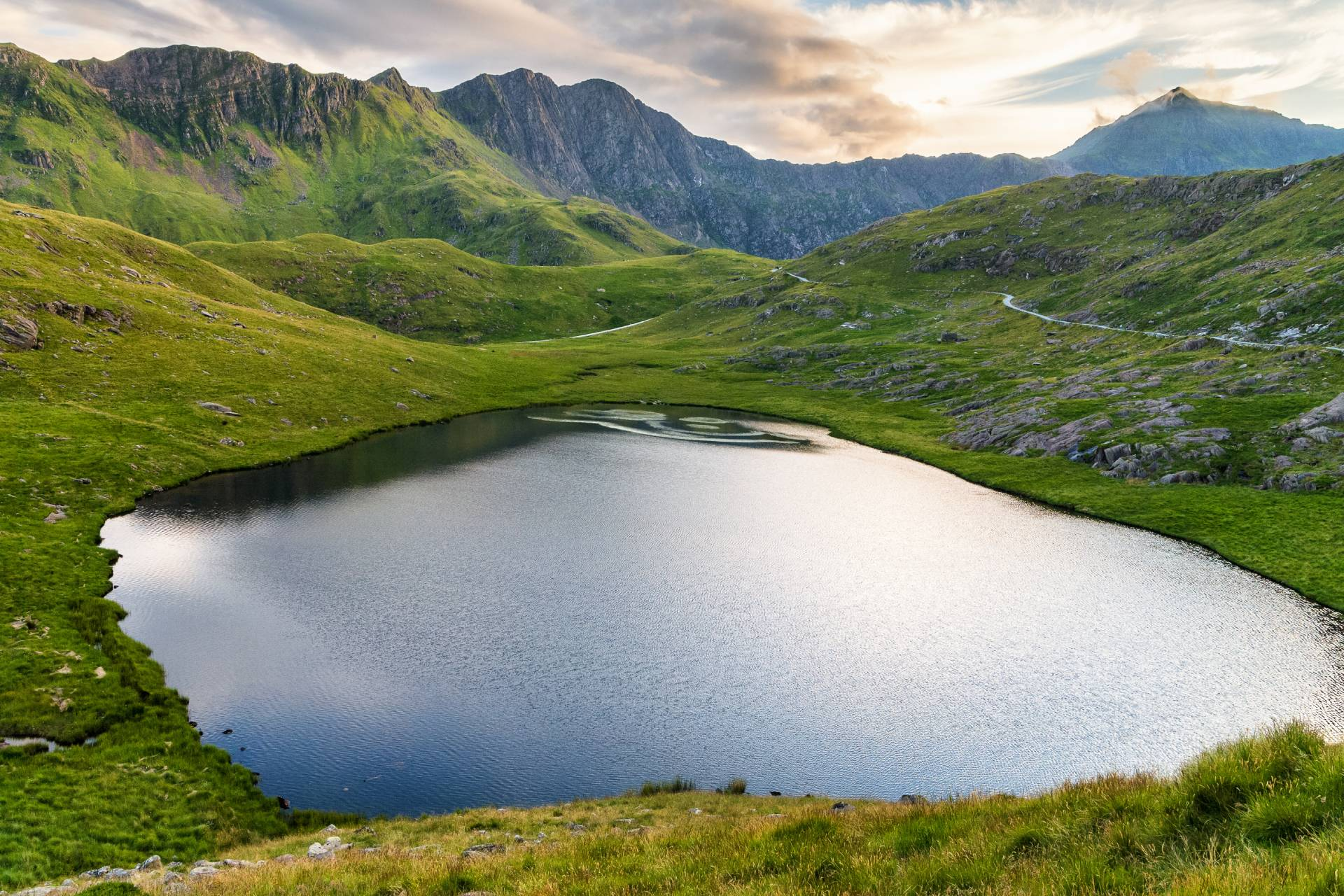 Lake called Llyn Teyrn under hiking pathway to Snowdon Peak called Miner´s track, Wales, Great Britain. Soft warm sunset light reflected in cool blue surface of the water.